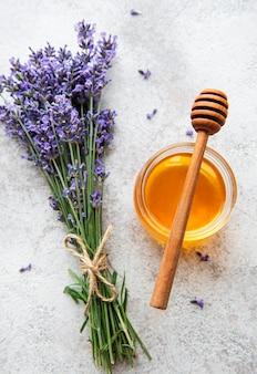 Glas mit honig und frischen lavendelblüten auf betonhintergrund