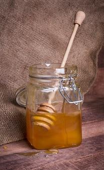 Glas mit honig und holzlöffel auf dem hintergrund