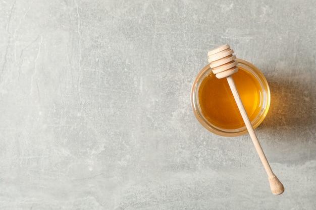 Glas mit honig und löffel auf grauem hintergrund, kopienraum