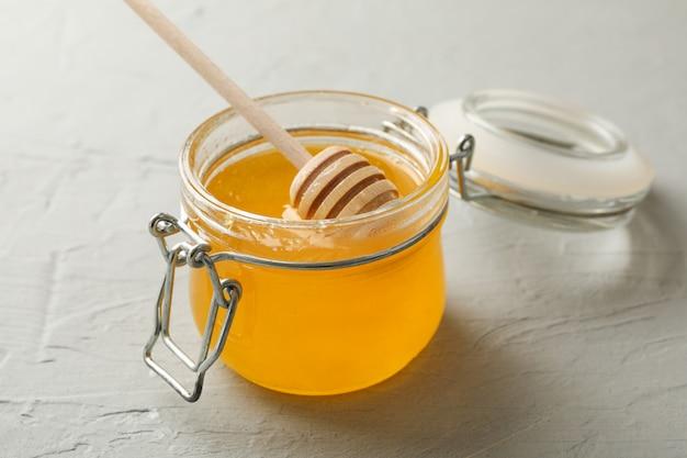 Glas mit honig und schöpflöffel auf weißem hintergrund
