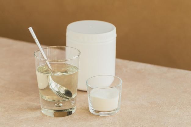 Glas mit in wasser gelöstem kollagen und kollagenproteinpulver auf einem hellbeigen tisch. gesundes lebensstilkonzept.