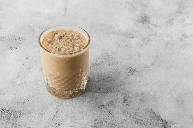 Glas mit kaltem kaffee und milch lokalisiert auf hellem marmorhintergrund. draufsicht, speicherplatz kopieren. werbung für cafe-menü. coffeeshop-menü. horizontales foto.