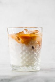 Glas mit kaltem kaffee und milch lokalisiert auf hellem marmorhintergrund. draufsicht, speicherplatz kopieren. werbung für cafe-menü. coffeeshop-menü. vertikales foto.
