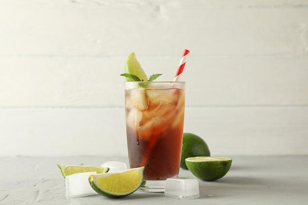 Glas mit kalter cola und zitrusfrüchten auf grauem zementhintergrund, platz für text