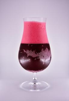 Glas mit kirschbierflüssigkeit und schaum