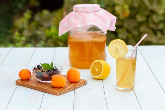 Glas mit kombucha, ein gegossenes glas mit kombucha mit einer zitronenscheibe, früchte auf einem holzbrett