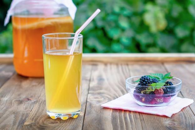 Glas mit kombucha, ein glas mit kombucha und eine tasse mit brombeeren in einem sommergarten.