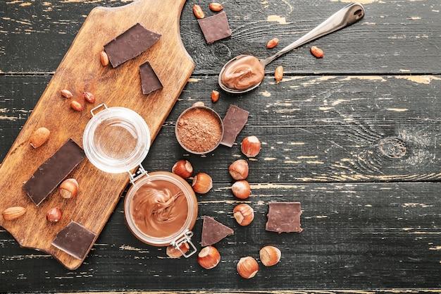Glas mit leckerer schokoladenpaste und haselnüssen auf dem tisch