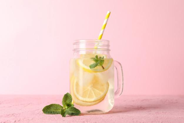 Glas mit limonade auf rosa oberfläche. frisches getränk