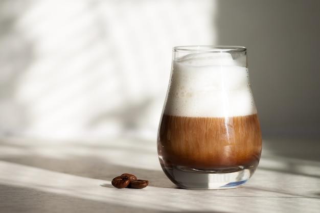 Glas mit milchigem kaffee latte oder cappuccino am morgen mit schönem sonnenlicht