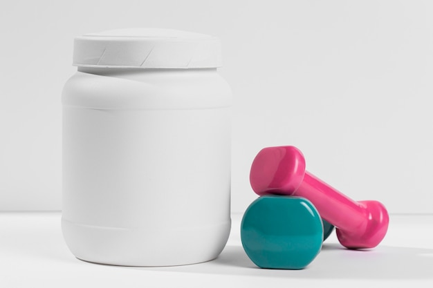 Glas mit nahrungsergänzungsmitteln und gewichten daneben