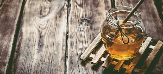 Glas mit natürlichem honig und einem löffel auf holztisch.