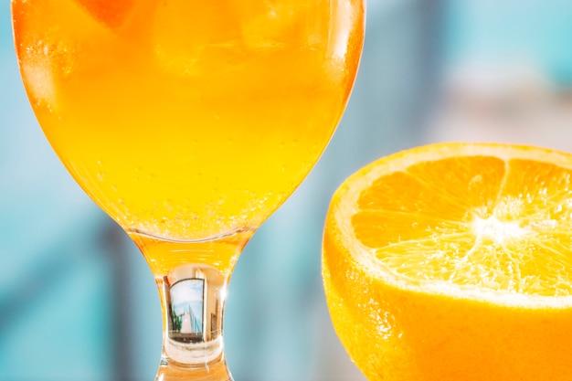 Glas mit orangengetränk und geschnittener orange