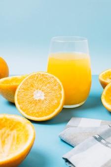 Glas mit orangensaft auf blauem hintergrund