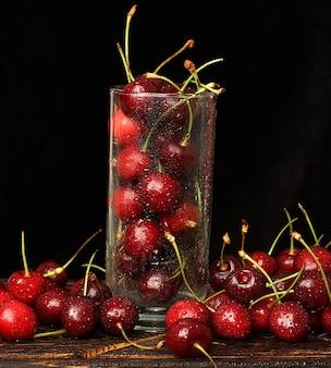 Glas mit reifen kirschen auf einem dunklen hintergrund mit wassertropfen.