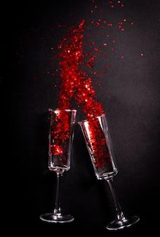 Glas mit rotem glitzer über schwarz, ferienwohnung lag