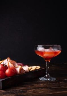 Glas mit rotem schnaps und wurstbrett, alkoholischer cocktail mit vorspeise, nahaufnahme.