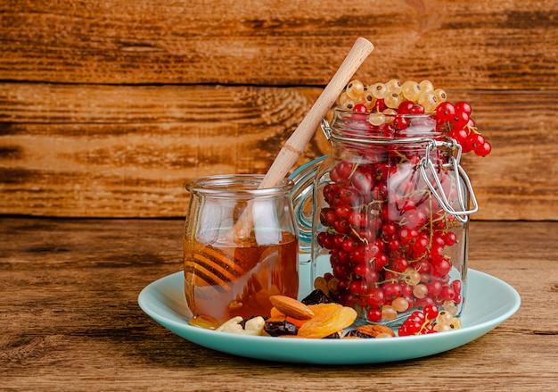 Glas mit roten johannisbeeren, honig, getrockneten früchten und nüssen auf holz