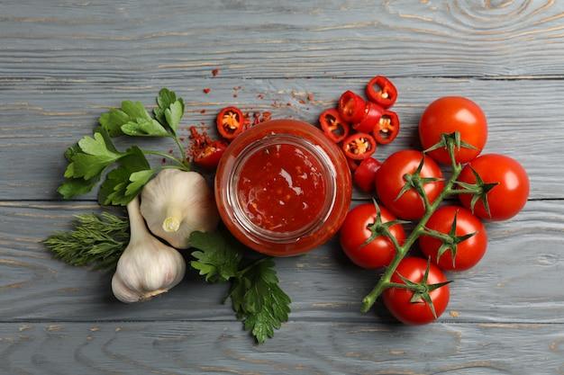 Glas mit roter chili-tomatensauce und gewürzen auf holztisch