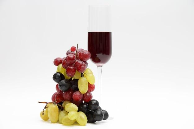 Glas mit rotwein mit trauben auf hellem hintergrund