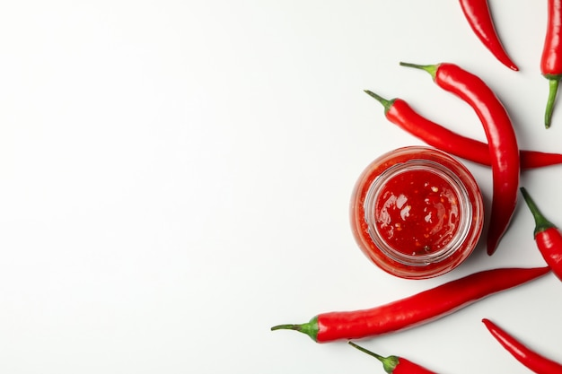 Glas mit sauce und chilipfeffer auf weißer wand, draufsicht
