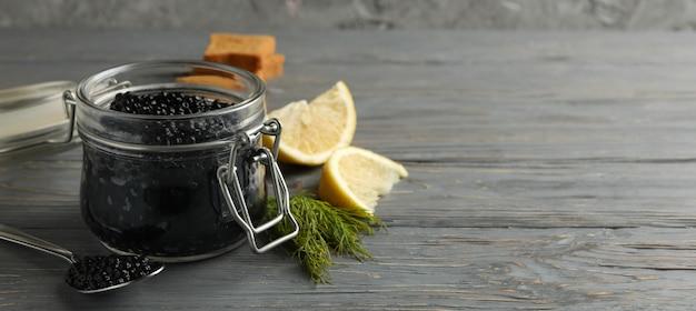 Glas mit schwarzem kaviar, brot, dill und zitrone auf hölzernem hintergrund, platz für text