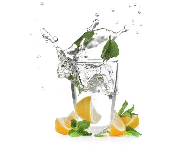 Glas mit spritzwasser und geschnittenen zitrusfrüchten auf weiß