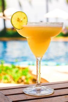 Glas mit süßem alkoholischem cocktail auf holztisch im exotischen erholungsort