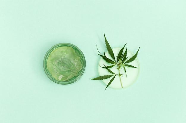 Glas mit transparentem kosmetikprodukt gel oder creme mit cannabisöl auf blau