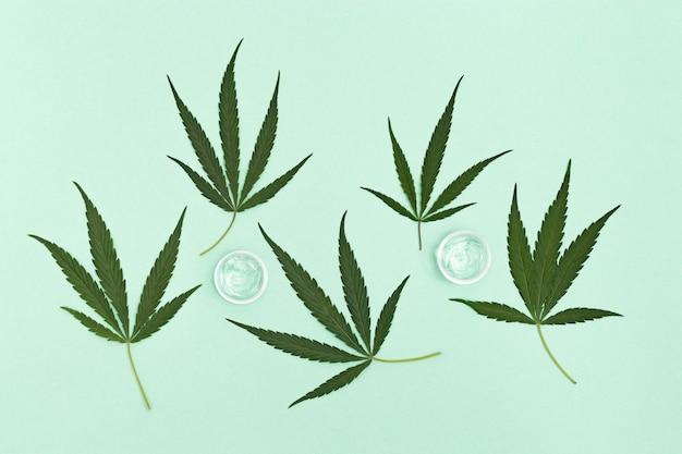 Glas mit transparentem kosmetischem produktgel oder creme mit cannabisöl auf grünem hintergrund