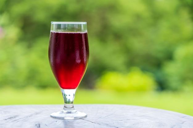Glas mit tropischem rotem saft vom blatthibiskus auf dem holztisch im hof, nah oben, tansania, ostafrika, kopienraum