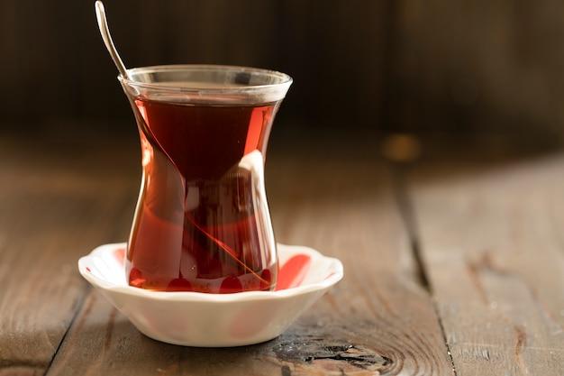 Glas mit türkischem tee auf holzbrett