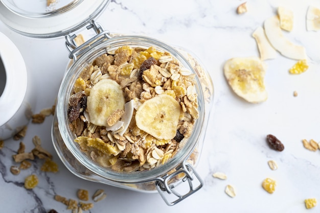 Glas mit vollkornprodukten zum frühstück. müsli mit getrockneten früchten und getrockneten früchten. mit kopierplatz. draufsicht.