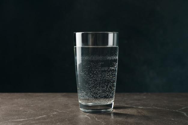 Glas mit wasser auf grauem tisch, nahaufnahme