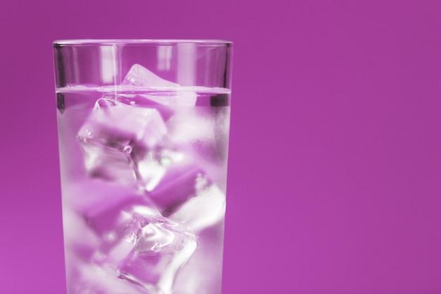 Glas mit wasser und eiswürfeln auf rosa hintergrund