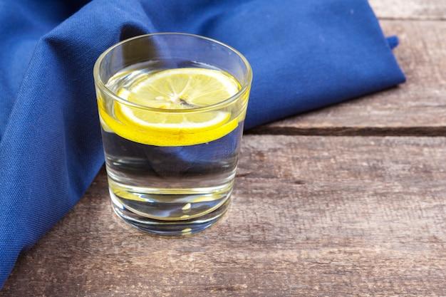 Glas mit wasser und zitrone auf holztisch
