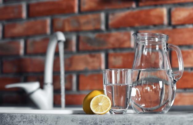 Glas mit wasser und zitrone auf küchentisch