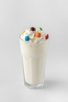 Glas mit weißem milchshake und sahne verziert mit bunten bonbons auf grauem hintergrund mit natürlichen schatten