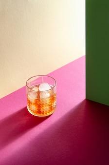 Glas mit whisky und eiswürfel auf tisch mit harten schatten. moderner isometrischer stil. kreatives konzept