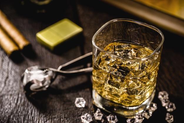 Glas mit whisky und eiszange auf holztisch