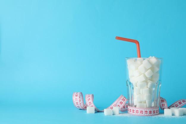 Glas mit zuckerwürfeln und maßband auf blauem hintergrund, platz für text