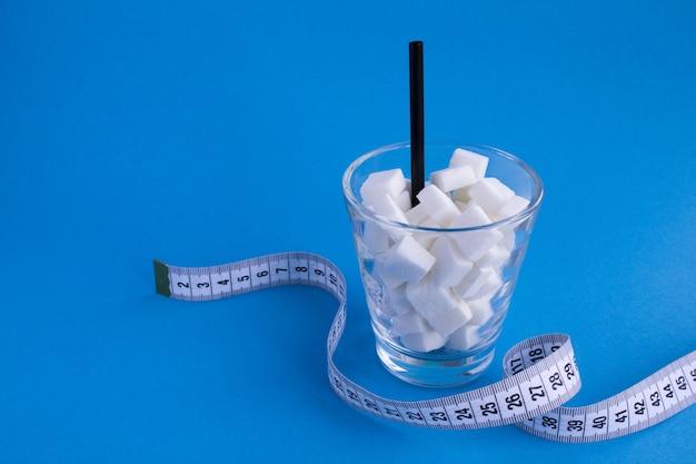 Glas mit zuckerwürfeln und weißem zentimeter auf dem blauen hintergrund. kopierraum. ungesundes lebensmittelkonzept.
