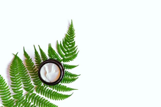 Glas natürliche bio-gesichtscreme auf farnblättern. kopieren sie platz für ihr kosmetikmarkendesign.