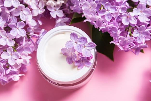 Glas natürliche gesichtscreme mit lila blumen auf rosa hintergrund