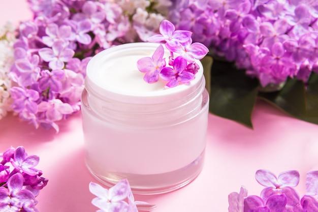 Glas natürliche gesichtscreme mit lila blumen auf rosa tisch