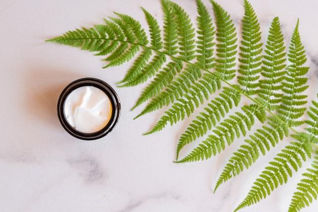 Glas natürliche organische gesichtscreme auf farnblättern auf marmorhintergrund. kopieren sie platz für ihr kosmetikmarkendesign.