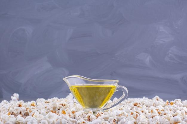 Glas olivenöl mit salzigem popcorn über stein