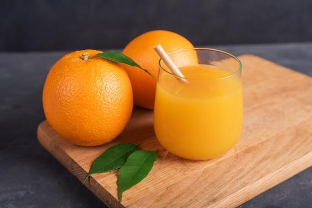 Glas orange und saft und orangenscheibe auf holzschreibtisch