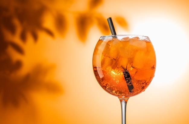 Glas orangen-aperol-spritz-cocktail auf defokussiertem blatthintergrund