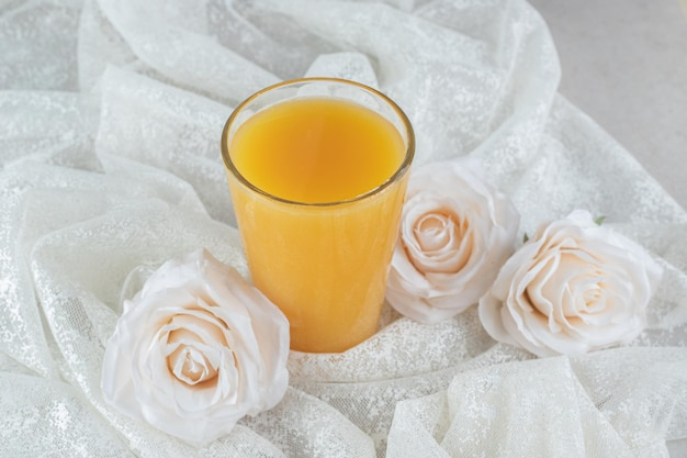Glas orangensaft mit blumen auf weißem stoff